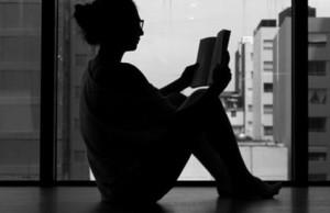 窓際で読書する女性