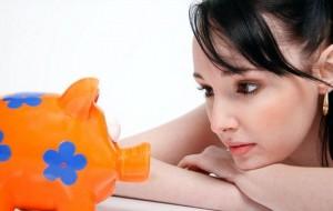 貯金箱を眺める女性