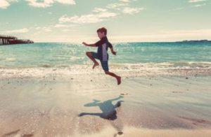 浜辺でスキップする少年