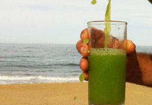 浜辺で青汁をそそぐ人