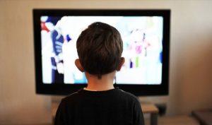 テレビにかじりついている少年