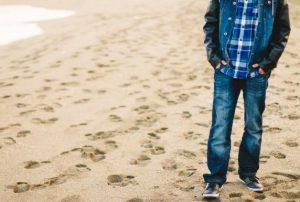 ジーパンで浜辺を歩く男性