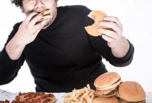 ハンバーガーをほおばる男性