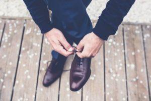 革靴の靴紐を結ぶ男性