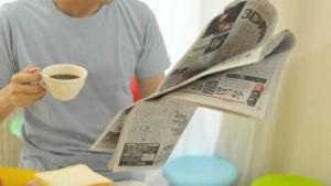 コーヒーを飲みながら新聞を読む男性