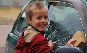 笑顔で洗車をする少年