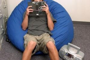 ビーズクッションの上で読書に没頭する男性