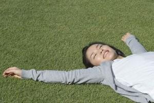 芝生で寝そべる女性