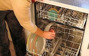 食洗器に皿をセットする女性