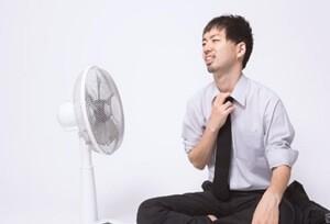 扇風機ですずむ男性