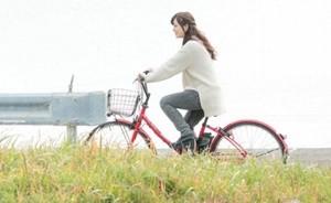 笑顔で自転車をこぐ女性