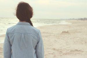 浜辺を見つめる孤独な女性