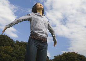 青空の下で背伸びをする女性