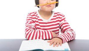 鼻の下に鉛筆を挟んでいる少女