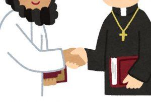 握手をするイスラム人と神父
