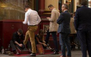 靴磨きの列に並ぶ紳士