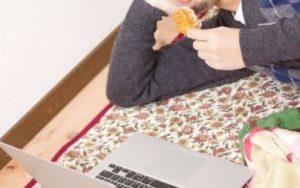 横になりながら煎餅を食べる男性