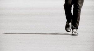 サンダルで歩く男性