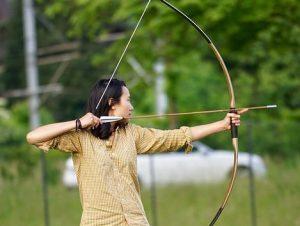 集中して矢を引く女性