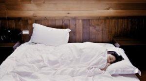 カーテンを洗濯して綺麗な寝室で眠る女性