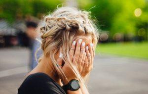 目を抑える金髪女性