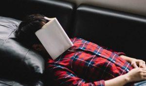 本を顔にのせて寝る男性